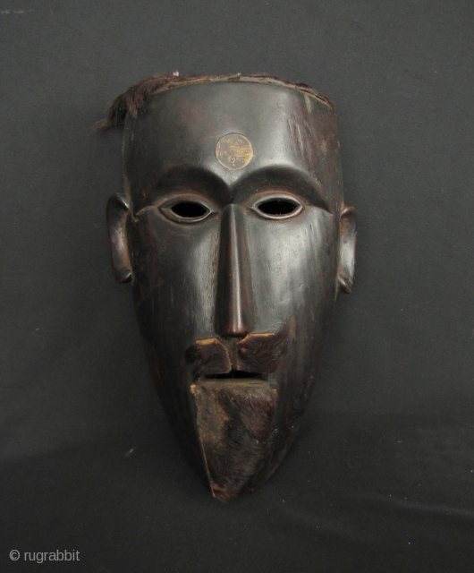 Nepalese Hill Tribe Mask: Well carved tribal mask from Nepal. This is made from a heavy, densely grained wood with an old Nepalese rupee set in the forehead and an animal hide goatee  ...