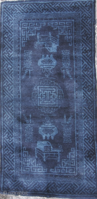 Good circa early 20th century blue rug with bogu pattern, i.e. displaying antique auspicious items. This has a classic Baotou color scheme consisting of all blue colors. The center medallion and vases  ...
