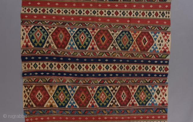"Caucasian kilim with spectacular colors.The White diamonds on the plain blue and red stripes are embroidered. An exceptional one of its type. 11'2"" x 5'4""."