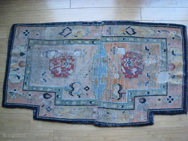 Old Tibet saddle cover, wool on cotton.  26 x 45 inches.  Holes for straps evident.  Somewhat faded.  Edges bound in dark blue wool, cotton upholstery backing.
