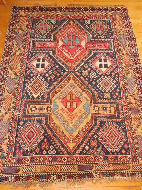 SHIRVAN WITH A DESIGN BURSTING WITH FOLK ART ELEMENTS.