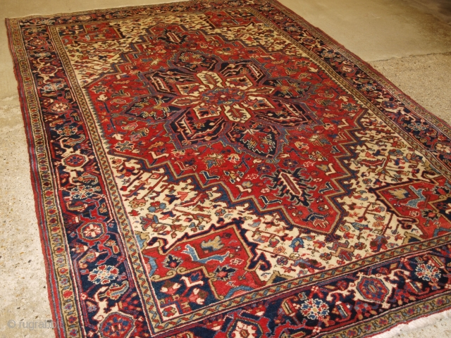 Antique Persian Heriz carpet with a traditional medallion design, medium red field colour with red and blue spandrels. Classic dark indigo blue border that is very well drawn. The central medallion in  ...
