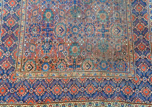 An antique Khorrasan carpet, some wear but complete, still retaining its original sides and fine blue kilim ends. 462x220cm. Early 19th century