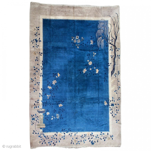 An elegant Peking rug with reduced asymmetric design. A narrow ivory border and a simple beige main border surround the medium blue central field. The asymmetric floral design in opposite corners creates  ...