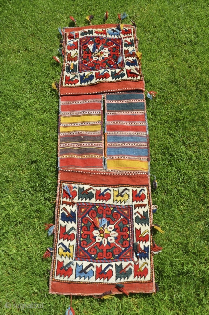 "West Anatolian pile heybe, Kilaz, 3'7"" X 1'4"". Wool. Circa 1900. Bright natural dyes. Faces in perfect condition with full pile and original pompom tassels. Striped back with a few stains. Dowry  ..."