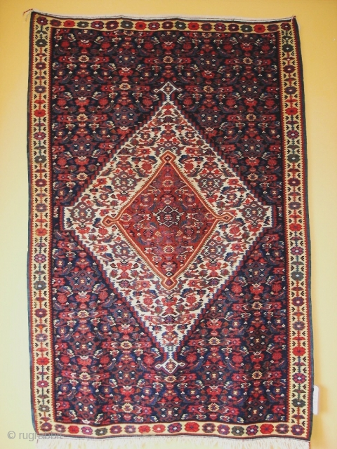 Antique Senneh kilim with dark blue background. Very good condition. Size is 115 x 175 cm.