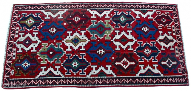 """Caucasian kilim with a brick red field and diagonal rows of large stepped concentric polychrome lozenges with a charcoal meandering angular border between serrated stripes, late 19c.  very good condition  136"""" x 70"""""""