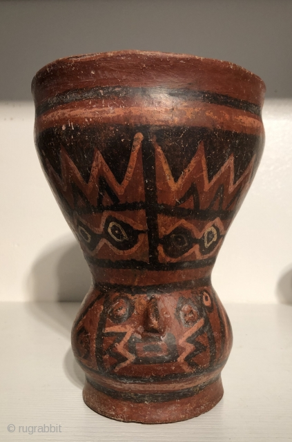Ancient polychrome ceramic drinking vessel with modeled human head depiction.  Lake Titicaca Basin. A.D. 800 - 1100.  This red-ware vessel is decorated with molded a human face and has a  ...