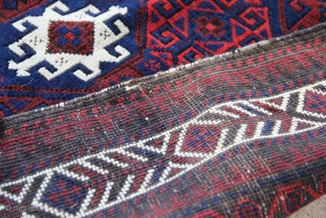 "PAir of antique Baluch bagfaces. Very shiny wool, typical moody Balouch combinations of navy blue, red and clever use of ivory. Each 2'8"" x 2'6"""