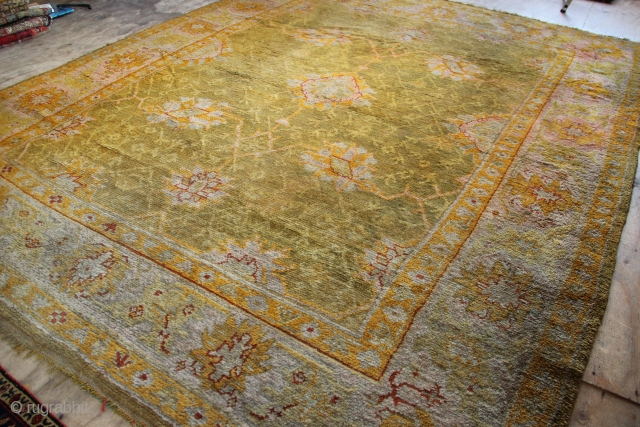 "Antique Oushak carpet in full pile and with no restoration- barring two sewn up fireplace cuts. Ultra decorative and rare carpet, in the unusual size of 9'8"" x 12'0""