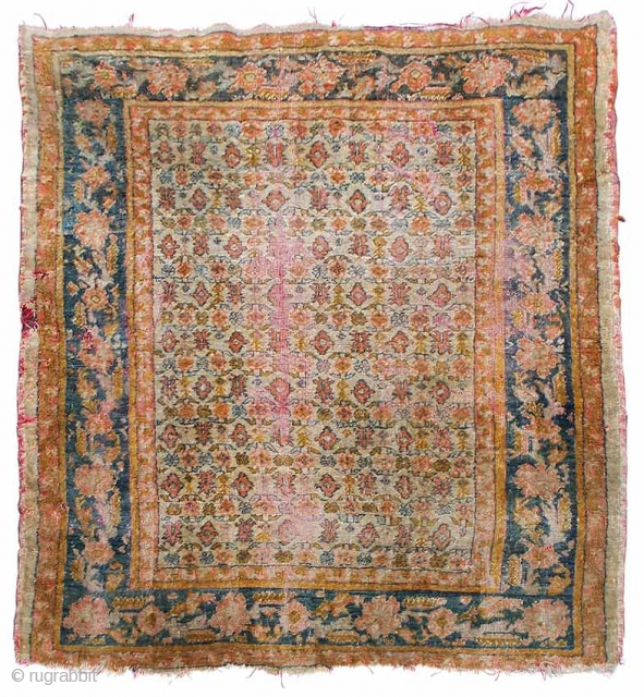 A small angora Oushak carpet, ivory field with allover floral and foliate design, blue main border with double guard bands, late 19th.century, areas of wear plus damages, 195 x 150cm.
