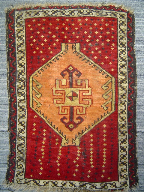 Anatolian yastik with amber hexagon spaceship medallion soaring over star-studded crimson field.  51 x 74 cm. -- Late 19th century.