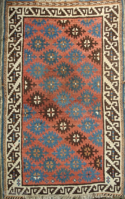 Antique Avar small rug with 30 Stars on Red Field and broad Ivory Border. 32 x 51 inches. Minor residue discolorations on verso.