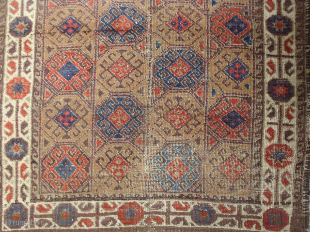 detail of colorful Antique Symmetrically knotted small Baluch rug with 40 Guls in rectangle lattice.