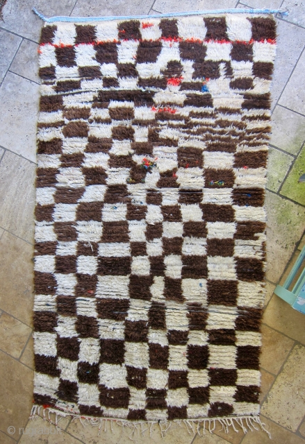 Azilal rug, middle Atlas mountain region of Morocco. Undyed cream and brown wool in a checker pattern on a cotton weft, with colorful boucherouite details of recycled cloth. Ca. 1980-1990. Has served  ...