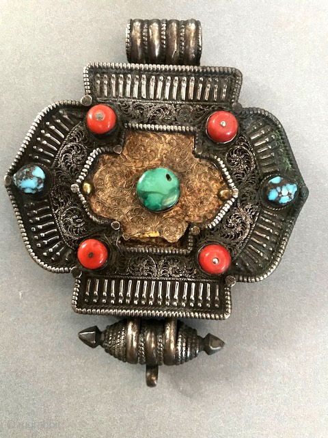 Tibetan silver gau with turquoise and coral and a sheet of gold in the front. late 19th or early 20th c