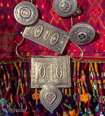 assorted Kazakh jewelry silver resting on Uzbek embroidered Torba
