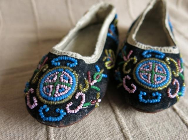 A pair of glass beaded children's shoes on velvet.