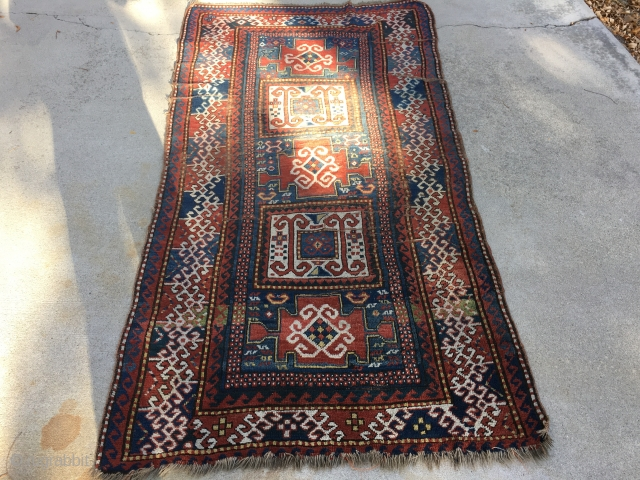 "As found: Late 1800's Kazak measuring 3'9"" to 4'1"" wide by 7'5"" long, has foundation showing, has four puckered wear area's, has minor loss of pile at one end, needs attention to  ..."