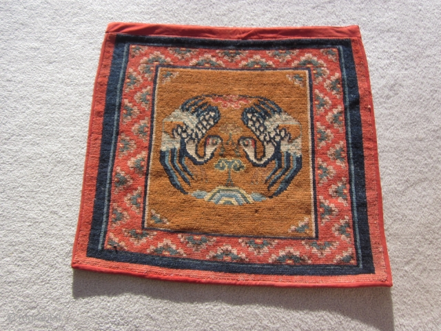Tibetan mat with two facing (and charming) naïve phoenixes nibbling on the tree of life motif. A country piece 27 by 29 inches in very good condition. Perhaps made about 1920.