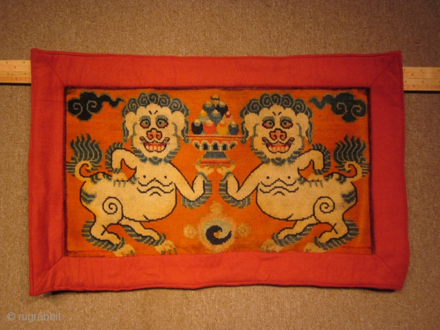 Tibetan mat with two grinning snow lions holding a bowl of flaming pearls, c.1930