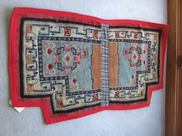 Tibetan notched saddle bottom, relatively uncrowded design on abrashed light blue field. Improvised border with small swastikas. Village product c.1930, very good condition. POR