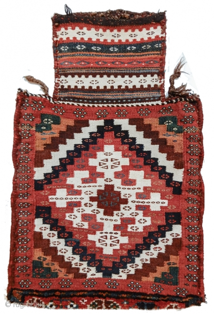This Luri-Bakhtiari ( or possibly Veramin ) salt bag is a graphic delight. A central cruciform element is drawn in white cotton against a deep rose madder ground, surrounded by diagonally radiating  ...