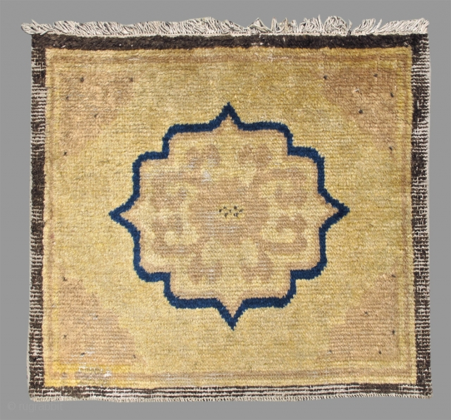 Chinese NingHsia seating square, A mirror back medallion drawn with indigo surrounds a lotus and vine-scroll calling to mind the Buddhist incantation ' the jewel in the lotus'. Faint but elegantly articulated  ...
