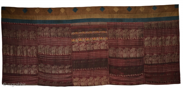 An antique Bhutanese hanging made of 5 panels of Indian-Assamese Vaishnavite silk lampas weave dyed with a red lac ground depicting scenes of humans, animals and Sanskrit writing. The hanging is mounted  ...