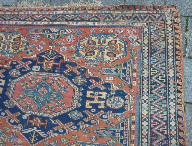 "Dated Kuba Sumakh 1877 ( 1294 ), 280 x 198 cm., 9' 2"" x  6' 6"". With patches, damages and lots of joyfully used faded early fuchsine dye."