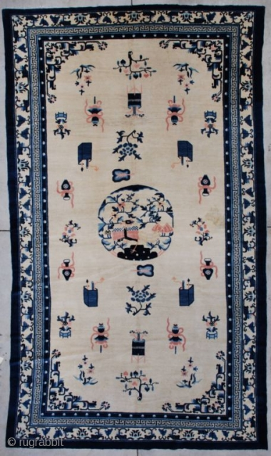 """This circa 1900 Peking Chinese Oriental carpet measures 7'2"""" X 12'1"""". It has an ivory field containing various Buddhist iconographies including the beribboned umbrella, paint boxes, standing urns, and several floral forms  ..."""