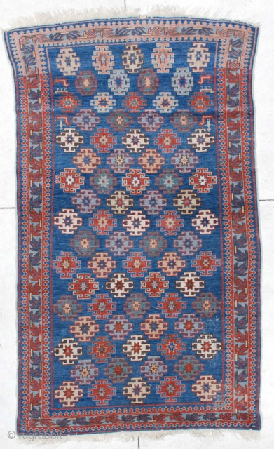 """#6471 Antique Kuba Oriental Rug  This 19th century antique   Kuba measures 3'9"""" X 6'4"""". It has latch hook medallions in red, ivory, yellow, green and pale blue on a medium blue  ..."""
