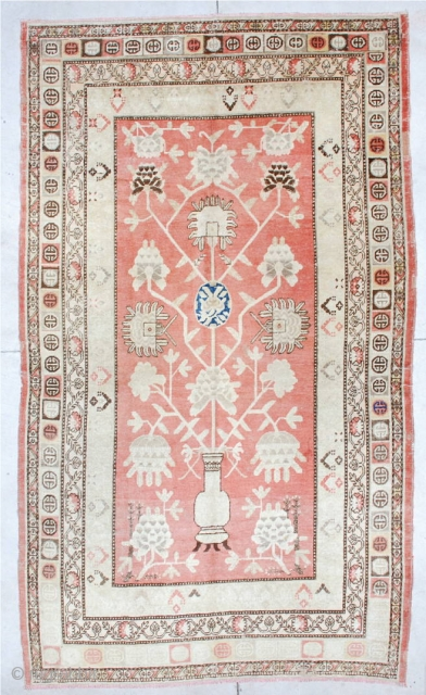 """#6683 Khotan  This Khotan measures 6'0"""" X 10'5"""". It has a salmon colored field containing a standing urn with a pomegranate tree growing out of it. The corners are worked in lotus blossoms.  ..."""