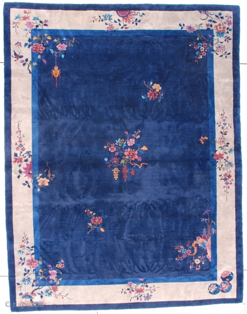 "This circa 1920 Art Deco Chinese Oriental Rug measures 9'0"" X 11'9"" (274 x 362 cm). It has a navy blue field containing a floral motif consisting of a rockery coming from  ..."