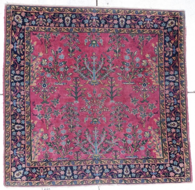 "This circa 1920 Sarouk measures 4'0"" X 4'0"". It has a dusty rose field with a one way floral design of trees and flowering branches all encompassed with a border of cypress  ..."