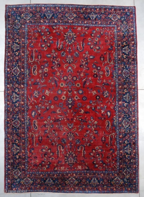 A circa 1900 antique Kerman measures 10' x 14' (305 x 427 cm). It has a red field with an overall floral motif in several shades of blue and ivory with some  ...