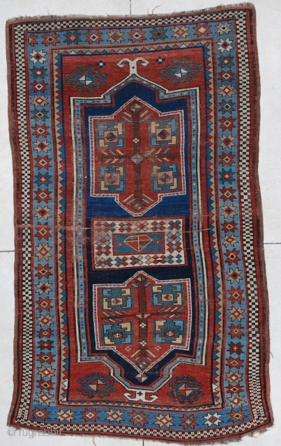 """#6640 Kazak This late 19th century Kazak measures 4'1"""" X 6'10"""". It has a double prayer motif in a Fachralo design. There are three medallions. Two in red and green and one in  ..."""