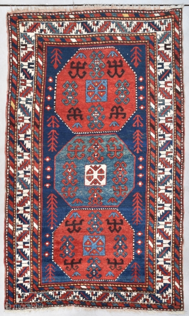 """#7734 Kazak Antique Rug  This circa 1880 Kazak Oriental Rug measures 4'7"""" X 7'8"""" (143 x 237cm). It has a dark blue ground with three eight sided medallions. The ones on the end  ..."""