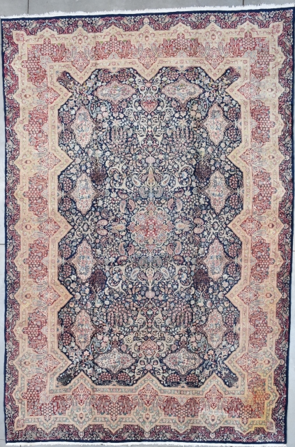 """#7794 Kerman Oriental Rug This antique Kerman Oriental Carpet which was bought new in 1927 measures 10'8"""" X 16'0"""". It has a dark blue field with twelve flower filled cartouches which are on  ..."""
