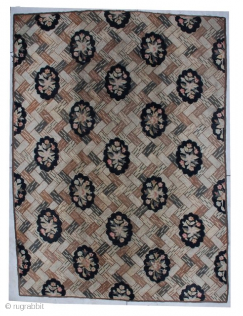 "This mid-19th-century American hooked rug measures 8'9"" x 11'11"". The background design is of different colored bricks displayed in the basket weave design.  There are diagonal rows of black scalloped ovals  ..."