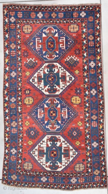 "This second half 19th century Kazak measures 4'7"" X 8'4"" (143 x 256 cm). This is a splendid Kazak. The tomato red ground sports four medallions in green and ivory. The medallions  ..."