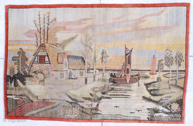 """This circa 1920 antique Khotan rug #6795 measures 5 '10"""" x 9' 0 """". It has a fantastically drawn scene of a house on the water with a lovely tiled roof sitting  ..."""