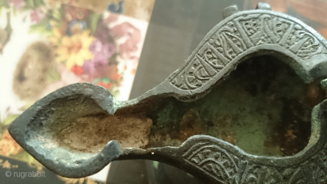 This is a cast bronze oil lamp from the Seljuq era in Khorassan, N.E. of Iran, ca. 12th century A.D. There is an inscription around the lid that I can not decipher.  ...