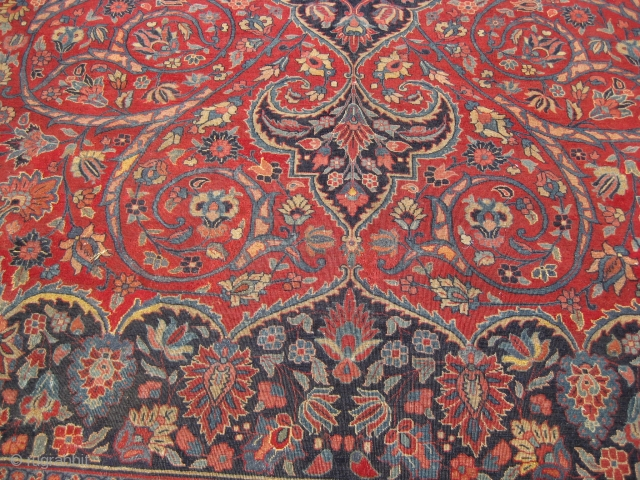 An old Persian dome medallion carpet with arabesque motif and sickle leaf border, consistent wear throughout with few repaired areas, 19 by 13 feet approximately.