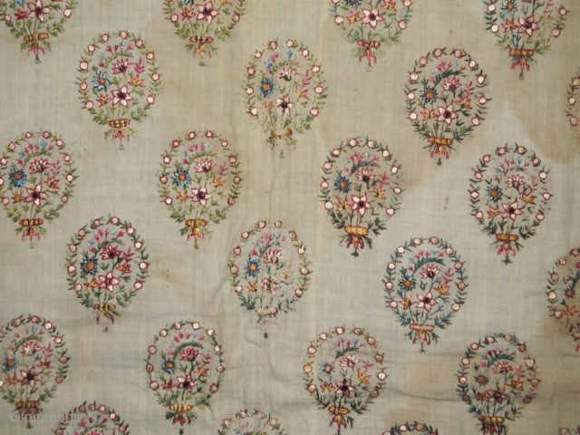 An old Mughal Embroidery, late19th c. Delicately embroidered silk bouquets on fine cotton base.  Complete piece with borders, but stained ground, wear in corners and old repair. Size:63x85cm