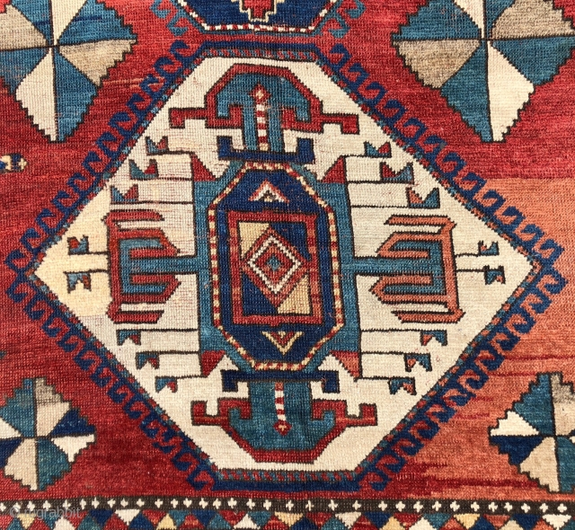 Antique large Kazak rug in fair condition with classic ivory Lori Pombak medallions. Good original natural colors with an abrashed tomato red ground and both light and dark blues. Overall good even  ...