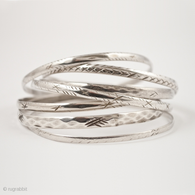 "Schnesshin, seven silver bangles, Tunis, Tunisia. 8"" (20.2 cm) interior circumference, Mid 20th century. Bangles are worn by Bedouin women in the city of Tunis in groups of seven, which is thought  ..."