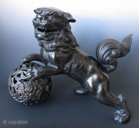 Playful Japanese Bronze Fu-dog on Ball Japanese bronze fu-dog and ball. The playful fu-dog stands with mouth open in a dynamic pose with back feet on the ground and front paws on the  ...