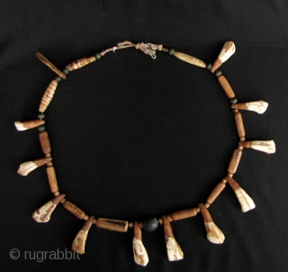 Chin Animal Bone Necklace: Eclectic strand of spherical wood, cylindrical bone and buffalo tooth beads, from the Chin ethnic group in Myanmar. Some of the bone beads have been dyed to resemble  ...