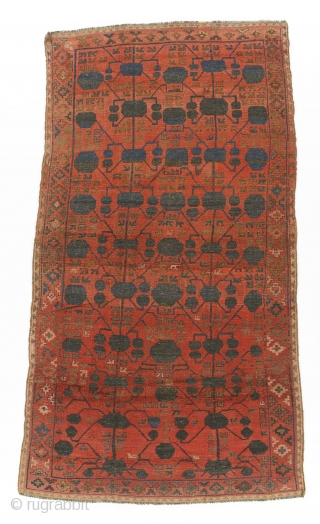 Kyrgyz giliam, Ferghana, Central Asia, late 19th century, 360 by 206 cm, an exceptionally rare for Kyrgyz carpets pomegranate design (Kashgar nuska) borrowed from Chinese Turkestan's silk carpets, natural colours, signed LR  ...